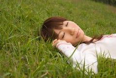 Jonge vrouwenslaap op gras Stock Fotografie