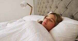 Jonge vrouwenslaap op haar bed stock videobeelden