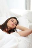 Jonge vrouwenslaap op het bed Stock Fotografie