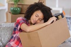 Jonge vrouwenslaap op kisten stock afbeeldingen
