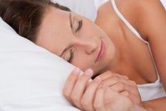 Jonge vrouwenslaap in wit bed Stock Fotografie