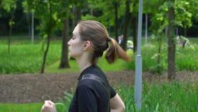 Jonge vrouwensprinter die in park bij zomer met groene gras Langzame motie lopen als achtergrond stock video