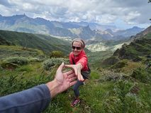 Jonge vrouwentoerist in alpiene streek in de zomer, man die haar helpen aan stock foto