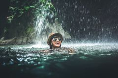 Jonge vrouwentoerist die bij de waterval in wildernissen zwemmen Het meisje van de het beeldreis van het eco-toerismeconcept Het  stock afbeeldingen