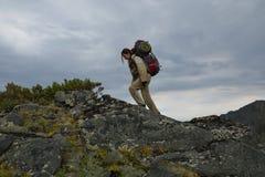 Jonge vrouwentoerist die bovenop de bergrand Barguzi lopen Royalty-vrije Stock Afbeeldingen