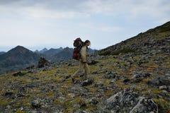 Jonge vrouwentoerist die bovenop de bergrand Barguzi lopen Stock Foto's