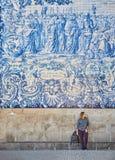 Jonge vrouwentoerist die dichtbij de kerk met beroemde Portugese blauwe keramische tegels op de voorgevel lopen die in Porto stad stock fotografie
