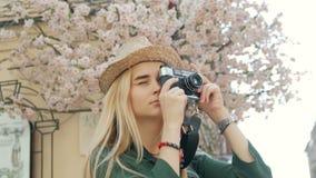 Jonge vrouwentoerist die een beeld op retro camera van een stad op vakantie nemen stock video