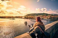 Jonge vrouwentoerist met een puppyhond en een rugzak die de toeristenboot bekijken en zwanen die op Vltava-rivier varen stock afbeeldingen