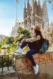Jonge vrouwentoerist voor het beroemde Sagrada Familia ori?ntatiepunt in Barcelona royalty-vrije stock foto's