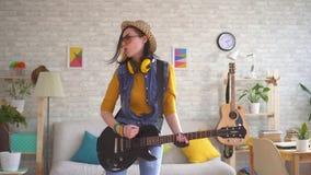 Jonge vrouwentuimelschakelaar die emotioneel het elektrische gitaar spelen hard in moderne flat spelen stock footage