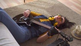 Jonge vrouwentuimelschakelaar die op de vloer liggen die elektrische gitaar, hoogste mening spelen stock videobeelden