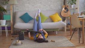 Jonge vrouwentuimelschakelaar die op de vloer liggen die de elektrische gitaar spelen die haar benen opheffen stock footage