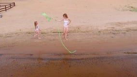 Jonge vrouwenturner in een wit lichaam op een zandig strand die met gymnastiek- lint dansen De zomer, dageraad stock videobeelden
