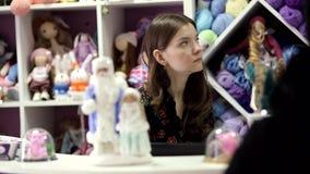 Jonge vrouwenverkoper bij de kleine winkel van ambachten stock videobeelden