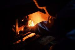 jonge vrouwenverlichting omhoog een brand in een traditionele open haard tijdens de koude wintermaanden stock afbeelding