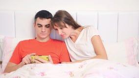 Jonge vrouwenverrassingen op berichten in haar man ` s telefoon stock video