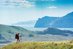 Jonge vrouwenwandelaar met rugzak en trekkingsstokken op een heuvel Royalty-vrije Stock Foto