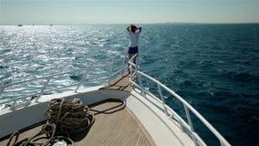 Jonge vrouwenwapens zoals vogelvleugels op jachtboot stock video