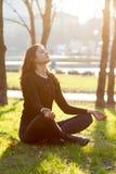Jonge vrouwenyoga die in park mediteren Stock Foto
