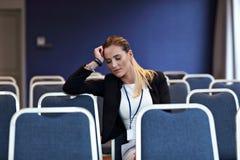 Jonge vrouwenzitting alleen in conferentieruimte Royalty-vrije Stock Fotografie