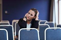 Jonge vrouwenzitting alleen in conferentieruimte Stock Afbeeldingen
