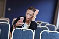 Jonge vrouwenzitting alleen in conferentieruimte Royalty-vrije Stock Foto's