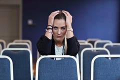 Jonge vrouwenzitting alleen in conferentieruimte Royalty-vrije Stock Afbeelding