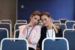Jonge vrouwenzitting alleen in conferentieruimte Stock Afbeelding