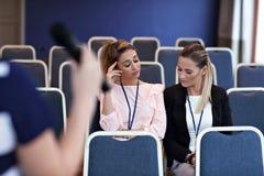 Jonge vrouwenzitting alleen in conferentieruimte Stock Fotografie