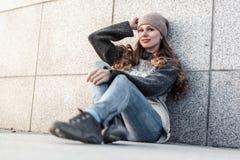 Jonge vrouwenzitting alleen naast granietmuur stock fotografie