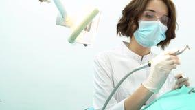 Jonge vrouwenzitting als tandvoorzitter op medisch examen op tandartskantoor media Zijaanzicht van mooie vrouwelijke tandarts stock video