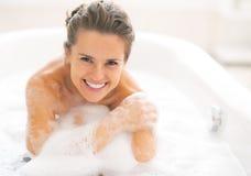 Jonge vrouwenzitting in badkuip stock foto's
