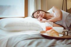Jonge vrouwenzitting in bed met een kop van melk Royalty-vrije Stock Foto's