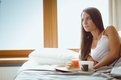 Jonge vrouwenzitting in bed met een kop van melk Stock Afbeeldingen
