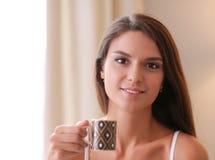 Jonge vrouwenzitting in bed met een kop van melk Royalty-vrije Stock Fotografie