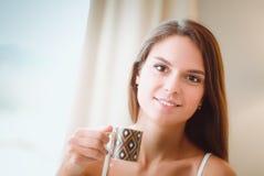 Jonge vrouwenzitting in bed met een kop van melk Royalty-vrije Stock Foto