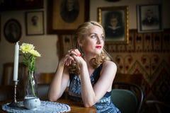 Jonge vrouwenzitting bij een lijst in een oude Europese koffie Royalty-vrije Stock Afbeeldingen
