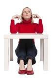 Jonge vrouwenzitting bij grappig klein bureau Royalty-vrije Stock Afbeeldingen