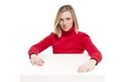Jonge vrouwenzitting bij grappig klein bureau Stock Afbeeldingen