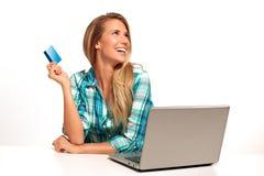 Jonge Vrouwenzitting bij het bureau die online winkelen Stock Foto