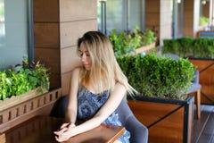 Jonge vrouwenzitting bij koffie en het rusten dichtbij ruimteinstallaties Stock Foto