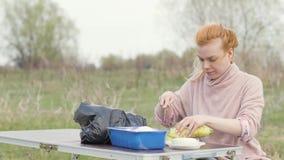 Jonge vrouwenzitting bij lijst en scherpe courgette voor picknick op aard stock videobeelden