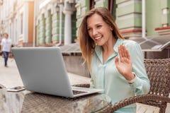 Jonge vrouwenzitting bij lijst in koffie die videogesprek hebben die aan ouders vrolijk glimlachen golven royalty-vrije stock foto's
