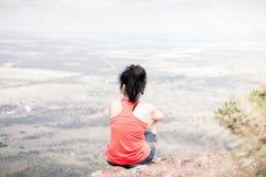 Jonge vrouwenzitting bij rand van klip Stock Foto