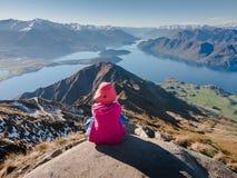 Jonge vrouwenzitting bij rand van klip die over expansieve mening van bergen en meren van Roys-Piek kijken royalty-vrije stock afbeelding