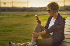 Jonge vrouwenzitting buiten met celtelefoon in een hand Stock Foto