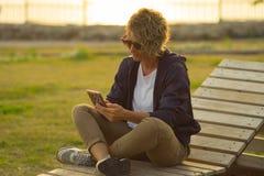 Jonge vrouwenzitting buiten met celtelefoon in haar handen Stock Foto's