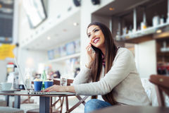 Jonge vrouwenzitting in de cafetaria met laptop en het gebruiken van mobiele telefoon royalty-vrije stock foto's
