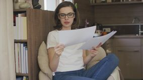 Jonge vrouwenzitting in de documenten van de leunstoellezing stock video